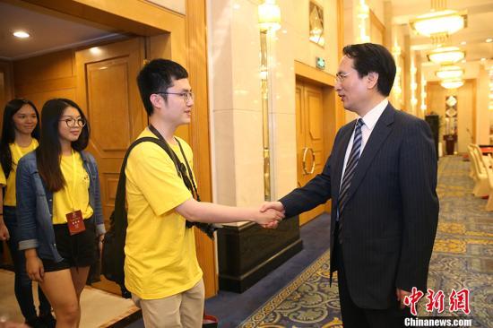 """7月26日,国务院侨务办公室副主任谭天星在北京会见加拿大华裔青少年""""中国寻根之旅""""夏令营全体营员。 中新社记者 韩海丹 摄"""