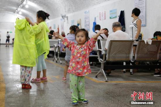 7月26日,小朋友在防空洞里玩耍。自今年入伏以来,浙江杭州已连续了十多日高温天气。为躲避酷暑,市民们来到防空洞里打牌看报,寻觅清凉。 中新社记者 王远 摄