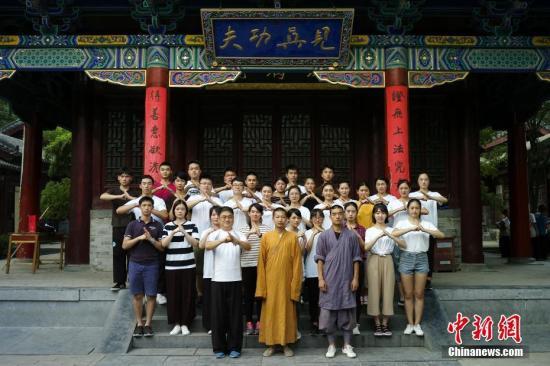 """7月24日,参加""""情系青春两岸青年中原行""""的30名青年来到河南少林寺,进行为期三天的武术训练。延康、延亚两位少林师父与学员们合影。中新社记者 杨程晨 摄"""