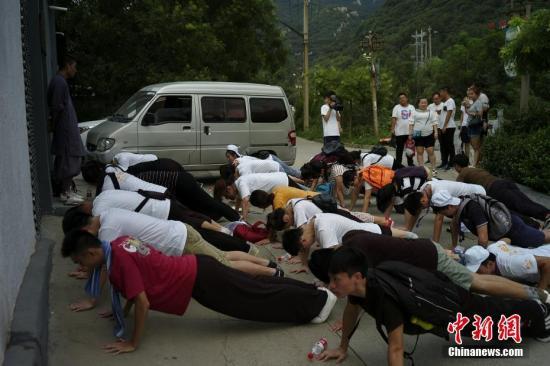 """7月24日,参加""""情系青春两岸青年中原行""""的30名青年来到河南少林寺,进行为期三日的武术训练。因学员走神,众人受罚做俯卧撑。中新社记者 杨程晨 摄"""