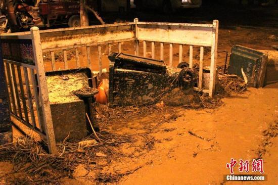 7月26日晚,陕西绥德县城被淤泥积水侵袭的镇定南路。 中新社记者 田进 摄
