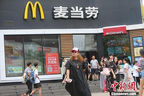 资料图:民众从山西太原一麦当劳前经过。中新社记者 张云 摄