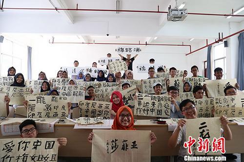 东盟国家学生和自己的书法作品合影留念。 <a target='_blank' href='http://www.chinanews.com/'>中新社</a>发 瞿宏伦 摄