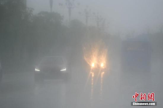 """7月31日,暴雨侵袭福州,路面能见度很低,许多车辆都开启大灯。今年第10号台风""""海棠""""(热带风暴级)的中心于7月31日2时50分前后在福建省福清市沿海登陆,登陆时中心附近最大风力有8级(18/米/秒),中心最低气压990百帕。中新社记者 王东明 摄"""