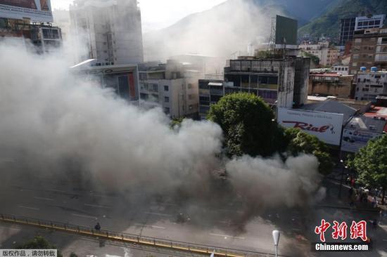 加拉加斯街头,一个警察局在冲突中被点燃,冒出浓烟。