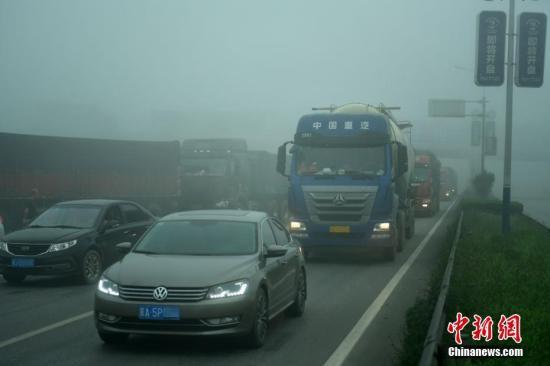 """资料图:大雾""""入侵""""河北。图为该省106国道车辆行驶缓慢。 记者 翟羽佳 摄"""
