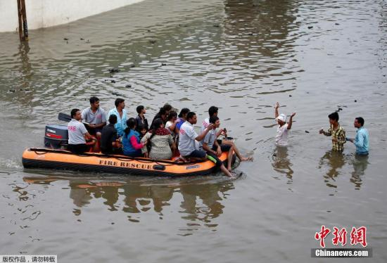 当地时间7月27日,印度艾哈迈达巴德,当地消防人员正在疏散被洪水围困的群众。