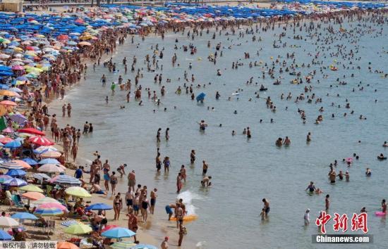 资料图:西班牙游客人数创新高,游客海滩扎堆场面壮观。