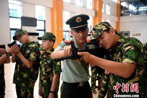 资料图:小学生在教官的指导下体验武器装备。中新社记者 韩苏原 摄