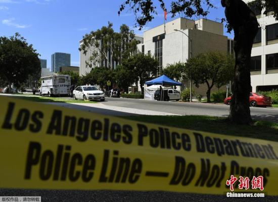 据报道,至少八个弹孔打穿建筑正门的玻璃门窗和金属门框,还有十数个弹孔落在建筑大楼正门的墙壁上。图为洛杉矶警方封锁现场。