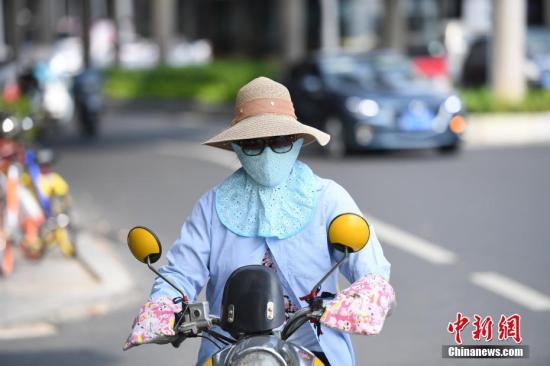 """8月2日,南宁持续高温天,市民""""捂装""""出行。连日来,持续走高的气温,让南宁进入闷热的""""桑拿天""""。中新社记者 俞靖 摄"""