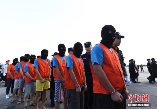 8月3日18时40分,一架印度尼西亚雅加达的航班抵达成都双流国际机场。58名嫌疑人被四川警方从印度尼西亚押解回国,6辆特警车辆将这批嫌疑人即刻转送案源地四川眉山市进一步调查处理。图为等待上押解车的犯罪嫌疑人。<a target='_blank' href='http://www.chinanews.com/'>中新社</a>记者 安源 摄