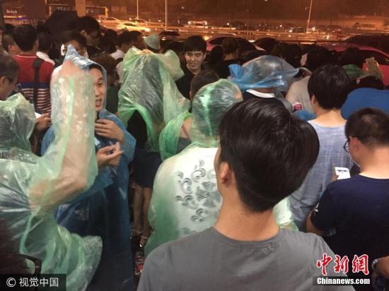 """8月2日傍晚,北京突降大雨,让很多上班族猝不及防,刚开始还是一片晴天,后来乌云覆盖,大雨来袭,很多民众都没带伞。地铁海淀五路居出站口处有免费领取雨衣,雨衣一会就被""""抢光""""。 姜志发 摄 图片来源:视觉中国"""