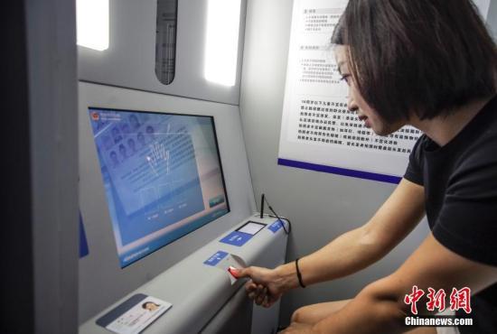 8月3日,北京市民正在身份证办理自助设备前办理业务。该设备从输入个人信息、照相、录指纹、交费到取证全程自助,几分钟内信息采集就可完成,照片不满意可重拍,24小时均可使用。图为在终端上采集指纹。<a target='_blank' href='http://auctionopia.com/'>中新社</a>记者 贾天勇 摄
