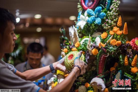 资料图:一名泰国男子用雕刻的水果和蔬菜拼成一件精心制作的装饰品。