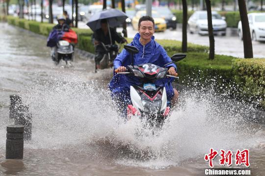 骑着电动车的市民涉水而行。 泱波 摄