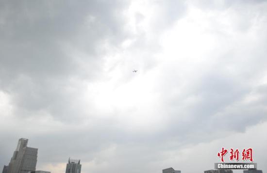 资料图:图为江西南昌上空,一架飞机从乌云中飞过。南昌市气象局发布雷电黄色预警信号。 中新社记者 刘占昆 摄