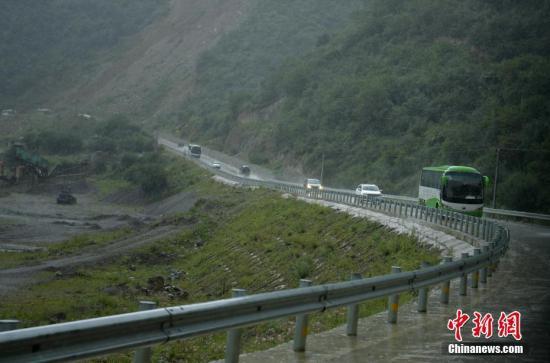 九寨沟震区最后一批游客安全转移。图为大客车载着游客冒雨撤离。 记者 刘忠俊 摄