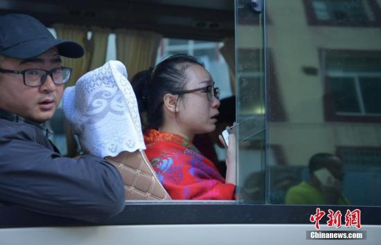 来自湖南的游客周女士(前)上车后边哭边用手机给家人报平安。 中新社记者 刘忠俊 摄