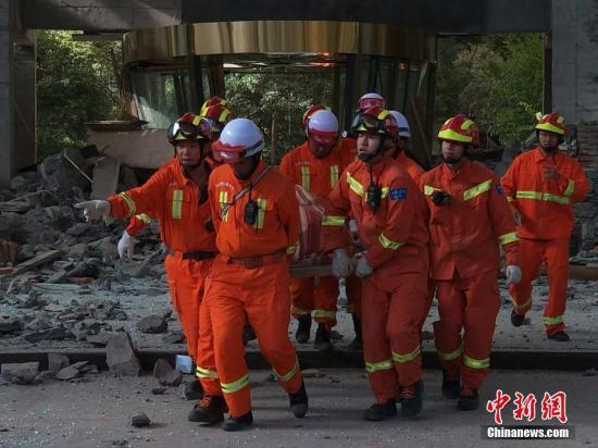 8月8日21时19分在四川阿坝州九寨沟县发生7.0级地震,震源深度20千米。图为8月9日,救援人员从受损建筑中救出一人。刘忠俊 摄