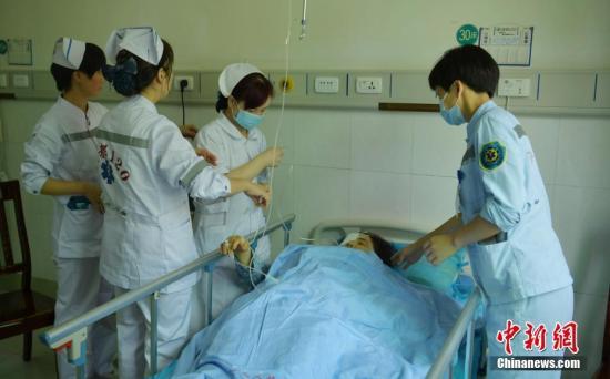 8月10日,四川九寨沟县人民医院,病房内医护人员正忙着救治地震伤者。地震发生后,四川400多名医护人员投入抢救伤员行动,190余名伤员已全部得到有效治疗,部分重伤员也已送往成都、绵阳等地救治。中新社记者 刘忠俊 摄