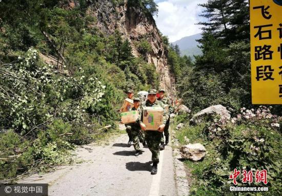 8月9日,四川阿坝,武警水电官兵搬运救灾物资前往九寨沟景区。图片来源:视觉中国
