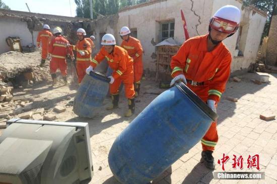 消防战士将受灾民众东西搬往安全地带。沈志君 摄
