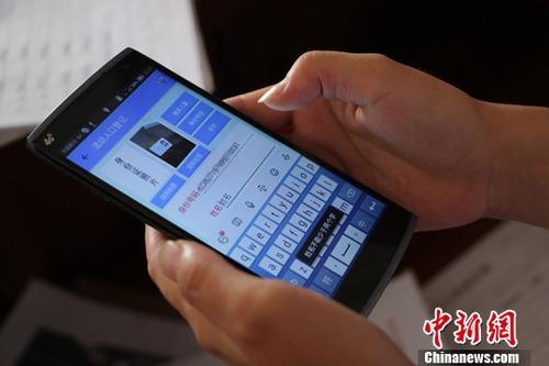 资料图:浙江台州一位网格员正在利用手机对租客进行身份信息确认。中新社记者 王刚 摄