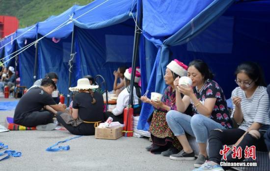 """8月10日,四川九寨沟""""8.8""""地震震源中心附近的临时安置点,受灾村民在帐篷边吃饭。中新社记者 刘忠俊 摄"""