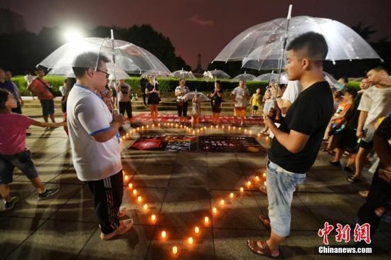 8月11日晚,众多市民来到湖南长沙烈士公园点亮电子蜡烛,撑起透明伞,为四川与新疆地震灾区的人们祈福。 杨华峰 摄