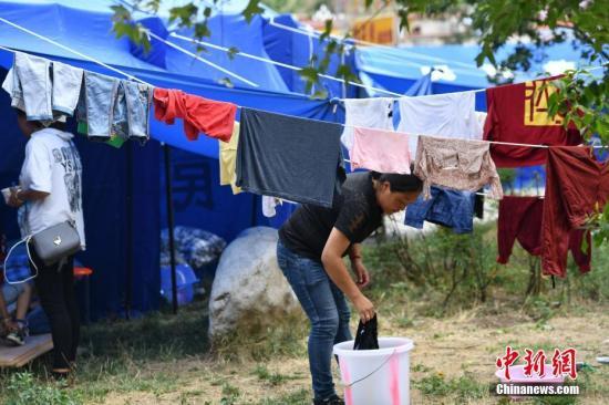 8月11日,九寨沟漳扎镇临时安置点内一名妇女正在晾晒衣物。当前,九寨沟地震灾区受灾民众生活在临时安置点内逐步恢复。 中新社记者 张浪 摄