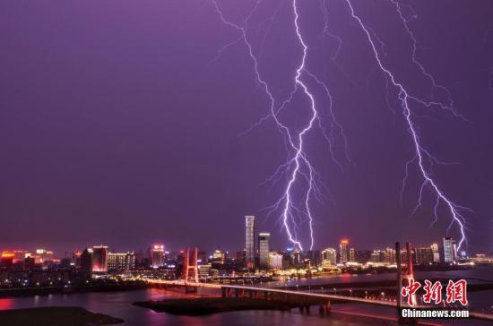 """8月12日晚间,江西省会南昌突降暴雨,城市夜空电闪雷鸣。长长的闪电不时划过天空,""""霹""""向高楼大厦,场景十分震撼。 江依 摄"""