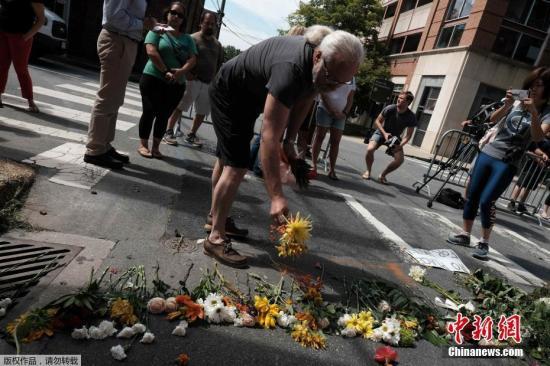 """当地时间2017年8月13日,美国弗吉尼亚州夏洛茨维尔市,民众在事发地点献花悼念遇难者。弗吉尼亚大学位于夏洛茨维尔市,当地时间12日爆发示威游行,各地的白人民族主义者和右翼活动人士来到这个大学城。警方预计这次集会人数多达2000到6000人,有机构称这可能是""""几十年来美国最大的一次仇恨集会""""。期间,一台银色汽车突然高速驶向人群,现场传来多阵尖叫声。从片段可见,在场民众起初未有意识到有人正要开车向他们袭来,相隔约10秒后才开始争相逃跑,现场陷入一片混乱。"""