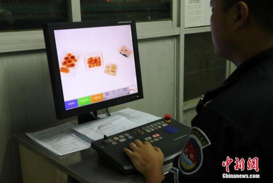 资料图:安检人员对货邮进行x光检查并填写申报单。记者 刘占昆 摄