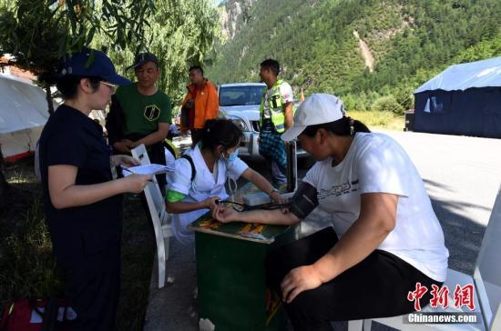 8月13日,记者走进九寨沟景区荷叶寨村民集中安置点,记者看到受灾民众已经住进临时安置的帐篷内,生活逐渐恢复正常。图为为村民测量血压。 安源 摄