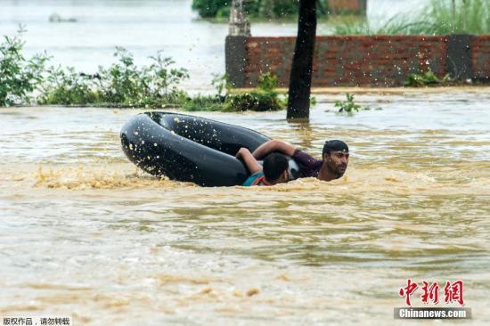 图为8月13日,尼泊尔比尔根杰帕萨区民众在洪水中。
