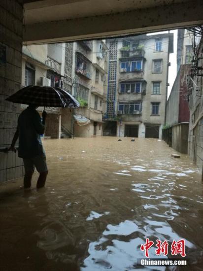8月14日,受流域内持续强降雨影响,广西柳州市融水苗族自治县融江河水暴涨,县城老城区被淹,居民只得乘船出行。这是融水县今夏第二次遭遇洪水袭击,距离上次被淹仅过了一个半月。据融水县防汛办信息,8月14日16时,融水水文站水位为111.65米(警戒水位10d6.6米)。目前,水位仍在上涨,柳州市已经启动防洪Ⅳ级应急响应。图为一名民众望着被洪水侵泡的家,欲涉水进入。蒙鸣明 摄