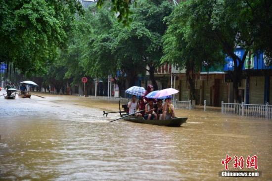 8月14日,受流域内持续强降雨影响,广西柳州市融水苗族自治县融江河水暴涨,县城老城区被淹,居民只得乘船出行。中新社记者 王以照 摄
