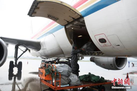 资料图:装卸人员开始把货物搬进飞机货仓。记者 刘占昆 摄