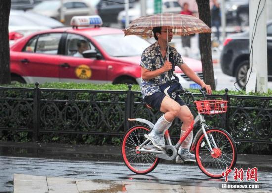 8月17日,辽宁沈阳的天气为小到中雨转雷阵雨,市民全副武装在雨中出行。当日,辽宁省气象灾害监测预警中心12时59分发布暴雨橙色预警信号。沈阳天气为小到中雨转雷阵雨。中新社记者 于海洋 摄