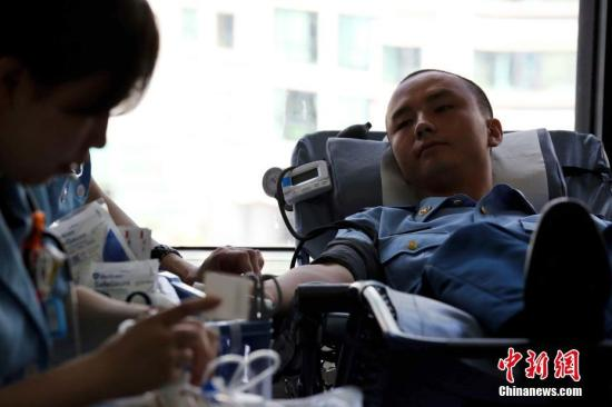 8月18日,驻港解放军空军战士在献血。当天,驻香港部队在枪会山军营医院组织无偿献血活动,400名官兵献血约16万毫升。参加此次活动的男性官兵为380名,女性官兵为20人,每人献血量分别为400毫升和350毫升。中新社记者 洪少葵 摄