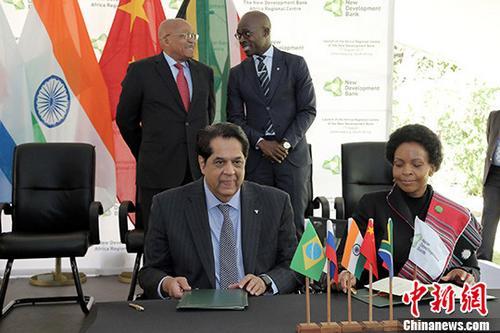 8月17日,金砖国家新开发银行非洲区域中心在约翰内斯堡正式成立。图为南非外交部长马沙巴内(前右)和新开发银行行长卡马特(前左)签署新开发银行非洲区域中心主办国协议,南非总统祖马(后左)与财政部长吉加巴见证。 中新社记者 宋方灿 摄