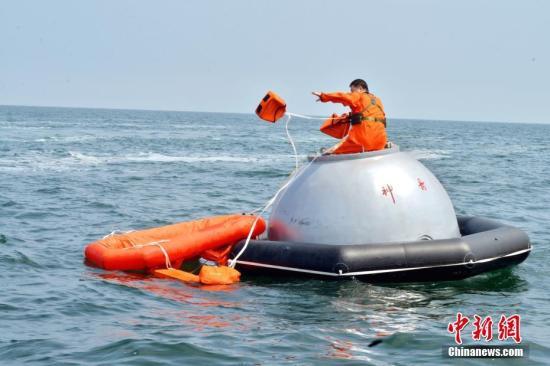 """16名中国航天员和2名欧洲航天员,8月21日在山东省烟台市附近海域圆满完成了为期17天的海上救生训练任务。图为训练期间,8月17日,航天员尝试从神舟飞船模拟返回舱""""逃离""""。 中新社发 朱九通 摄"""
