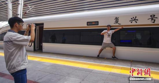 """8月21日,开往石家庄的G9061次""""复兴号""""动车组列车在北京西站迎接旅客。 <a target='_blank' href='http://www.chinanews.com/'>中新社</a>记者 贾天勇 摄"""