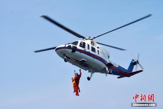 16名中国航天员和2名欧洲航天员,8月21日在山东省烟台市附近海域圆满完成了为期17天的海上救生训练任务。图为训练期间,8月17日,直升机悬吊营救训练。 中新社发 朱九通 摄