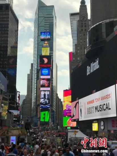 21日当天,纽约时报广场上的大屏幕(中间由上往下第三块)正在直播日全食过程。 <a target='_blank' href='http://chupinj.com/'>中新社</a>记者 马德林 摄