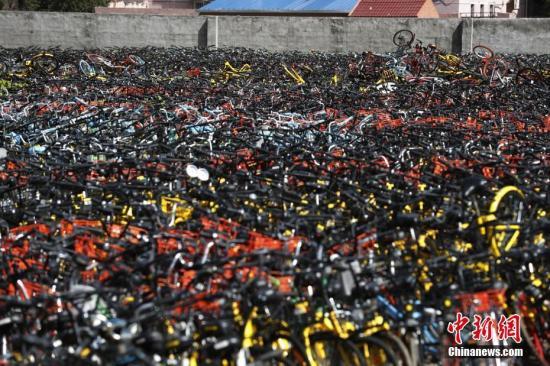 资料图:在上海静安区某违停非机动车堆放现场,上万辆各种颜色的共享单车被摆放的密密麻麻。 张亨伟 摄