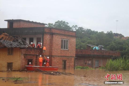 """8月24日上午,受强台风""""天鸽""""影响,广西钦州全市普降大雨,当地一村庄由于持续的强降雨导致突发大水,有4名民众被约3米深的洪水围困在危房中。经过两个小时的救援,4名被困人员被当地消防官兵用冲锋舟成功救出,并转移至安全区域。图为消防官兵成功到达被困地点。 中新社记者 何业燊 摄"""