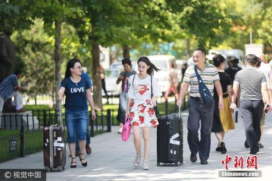 资料图:大学新生在家长陪同下入学报到。 图片来源:视觉中国