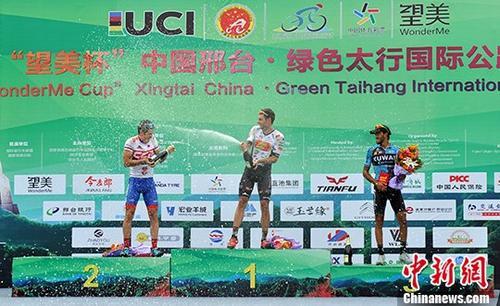 图为本赛段前三名选手上台领奖开香槟庆祝。 中新社记者 韩冰 摄